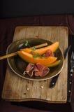 与熏火腿的橙色瓜 库存图片