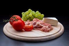 与熏火腿,乳酪,葡萄,蕃茄的开胃小菜 库存图片