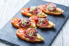 与熏火腿,蕃茄,在ciabatta面包的夏南瓜的开胃菜bruschetta在石板岩背景关闭 免版税库存图片