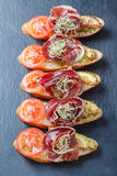 与熏火腿,蕃茄,在ciabatta面包的夏南瓜的开胃菜bruschetta在石板岩背景关闭 免版税库存照片