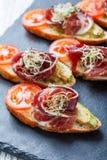 与熏火腿,蕃茄,在ciabatta面包的夏南瓜的开胃菜bruschetta在石板岩背景关闭 库存照片