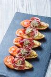 与熏火腿,蕃茄,在ciabatta面包的夏南瓜的开胃菜bruschetta在石板岩背景关闭 库存图片