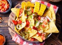 与熔化乳酪调味料、辣调味汁和玉米棒子的烤干酪辣味玉米片在木背景顶视图的碗 免版税库存照片