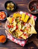 与熔化乳酪调味料、辣调味汁和玉米棒子的烤干酪辣味玉米片在木背景顶视图的碗 库存图片