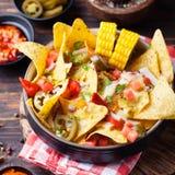 与熔化乳酪调味料、辣调味汁和玉米棒子的烤干酪辣味玉米片在棕色木背景的碗 免版税库存照片
