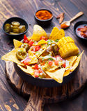 与熔化乳酪调味料、辣调味汁和玉米棒子的烤干酪辣味玉米片在棕色木背景的碗 图库摄影