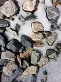 与熔化的雪后面地面的岩石 免版税库存图片
