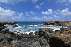 与熔岩岩石的美丽的小海湾沿阿鲁巴` s东海岸 免版税库存照片