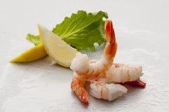与熟食店叶子和柠檬的蒸的超大无首的虾在白色背景的白色板材 免版税库存图片
