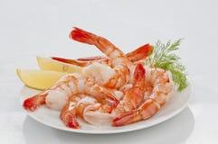与熟食店叶子和柠檬的蒸的超大无首的虾在白色背景的白色板材 库存图片