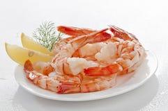 与熟食店叶子和柠檬的蒸的超大无首的虾在白色背景的白色板材 免版税库存照片