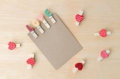 与爱夹子和红色心脏的白纸笔记在木backgr 免版税库存照片