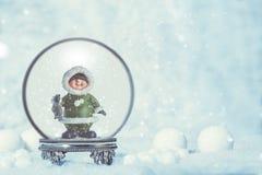 与爱斯基摩的Snowglobe在季节性背景中 免版税库存图片