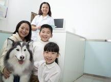 与爱犬的家庭在兽医的办公室 免版税库存照片