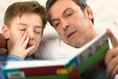 与父亲的上床时间读书 免版税库存照片