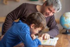 与父亲的年轻矮小的shoolboy解决的数学家庭作业 免版税库存照片