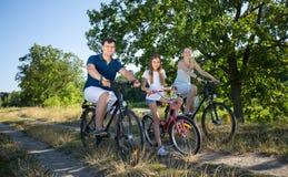 与父母的女孩骑马自行车的在草甸晴天 联系人 免版税库存图片