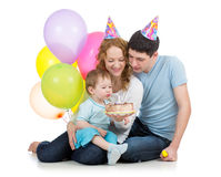 与父项的孩子庆祝生日和在蛋糕的吹的蜡烛 免版税库存照片