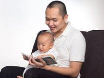 与爸爸的阅读书 免版税库存照片
