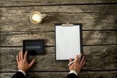 与片剂、纸和咖啡的商人在表上 免版税库存照片
