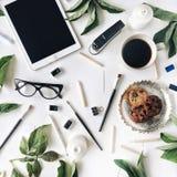与片剂、玻璃、杯子无奶咖啡,曲奇饼在金黄盘子,铅笔、油漆刷和叶子的工作区 免版税库存照片