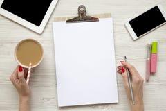 与片剂、noticepad、板料、拿铁、智能手机和女性的女性工作区移交白色木背景, 免版税库存照片