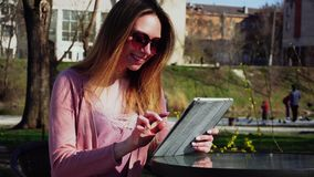 与片剂一起使用在公园和休息在太阳镜的迷人的女孩 股票录像