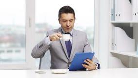 与片剂个人计算机和咖啡杯的微笑的商人 股票视频
