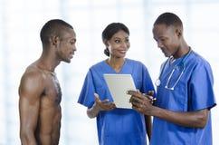 与片剂个人计算机和患者的非洲医疗保健队 库存照片