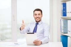 与片剂个人计算机和文件的微笑的商人 免版税库存照片