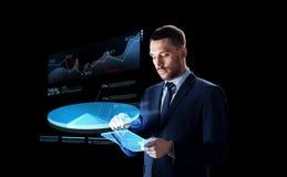 与片剂个人计算机和真正圆形统计图表的商人 免版税库存图片