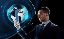 与片剂个人计算机和真正地球的商人 免版税图库摄影