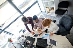 与片剂个人计算机和纸的企业队在办公室 库存图片