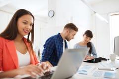 与片剂个人计算机和纸的创造性的队在办公室 免版税图库摄影