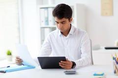 与片剂个人计算机和纸的商人在办公室 免版税库存图片