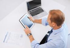 与片剂个人计算机和纸的商人在办公室 免版税图库摄影