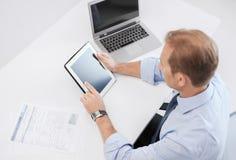 与片剂个人计算机和纸的商人在办公室 免版税库存照片