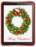 与片剂个人计算机框架的圣诞节花圈 库存照片
