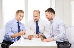 与片剂个人计算机的三个微笑的商人在办公室 图库摄影