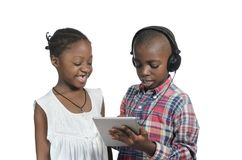 与片剂个人计算机的两个非洲孩子 免版税库存照片