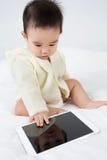 与片剂个人计算机的亚洲婴孩戏剧比赛 免版税库存图片