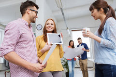 与片剂个人计算机的创造性的队谈话在办公室 免版税库存照片