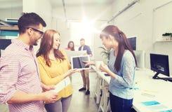 与片剂个人计算机的创造性的队谈话在办公室 库存照片