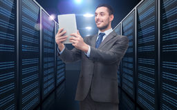与片剂个人计算机的商人在服务器室 免版税图库摄影