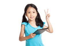 与片剂个人计算机的小的亚洲女孩展示胜利标志 图库摄影