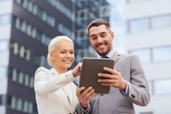 与片剂个人计算机的微笑的商人户外 免版税库存图片