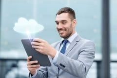 与片剂个人计算机的微笑的商人户外 库存图片