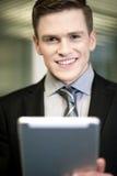 与片剂个人计算机的微笑的商人 库存照片