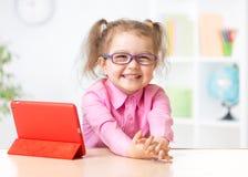 与片剂个人计算机的愉快的孩子在玻璃作为及早 库存图片