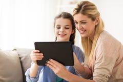 与片剂个人计算机的愉快的家庭在家 免版税库存照片